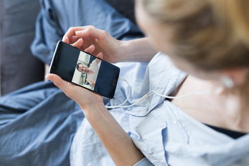 Frau zu Hause, die sich auf der Couch entspannt und während der Coronavirus-Pandemie soziale Medien am Telefon für Video-Chats mit ihren Lieben nutzt. Zu Hause bleiben, sozial distanzierender Lebensstil.