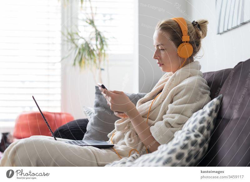 Soziale Distanzierung. Bleiben Sie zu Hause. Frau im Bademantel, die es sich auf ihrem Sofa zu Hause gemütlich macht und Social-Media-Anwendungen am Telefon für Video-Chats und Styling mit ihren Lieben nutzt.