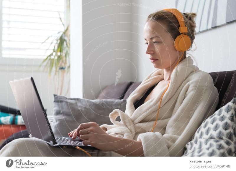 Bleiben Sie zu Hause und distanzieren Sie sich von der Gesellschaft. Frau im lässigen Hausbademantel, die fern vom Wohnzimmer arbeitet. Video-Chat über soziale Medien mit Freunden, Familie, Geschäftskunden oder Partnern.