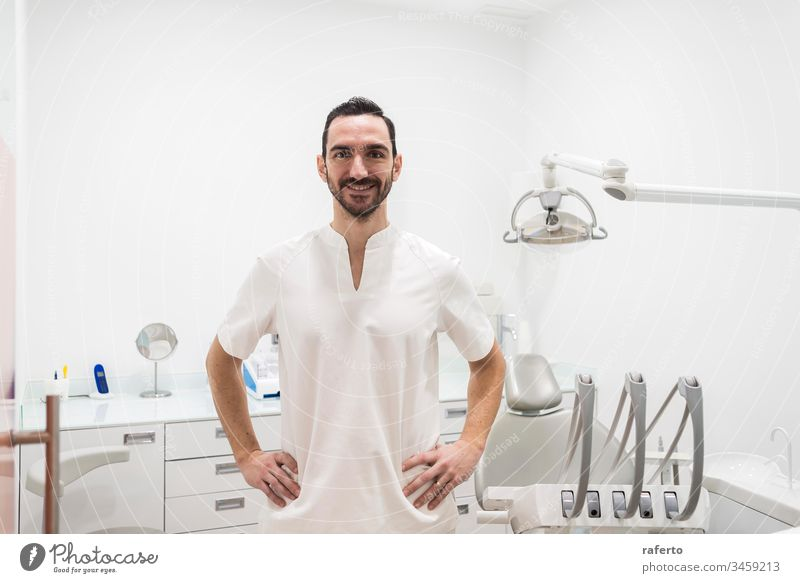 Porträt eines lächelnden männlichen Arztes, der in einer Zahnarztpraxis posiert Klinik Glück Gesundheitswesen dental Pflege bärtig professionell Zahnmedizin