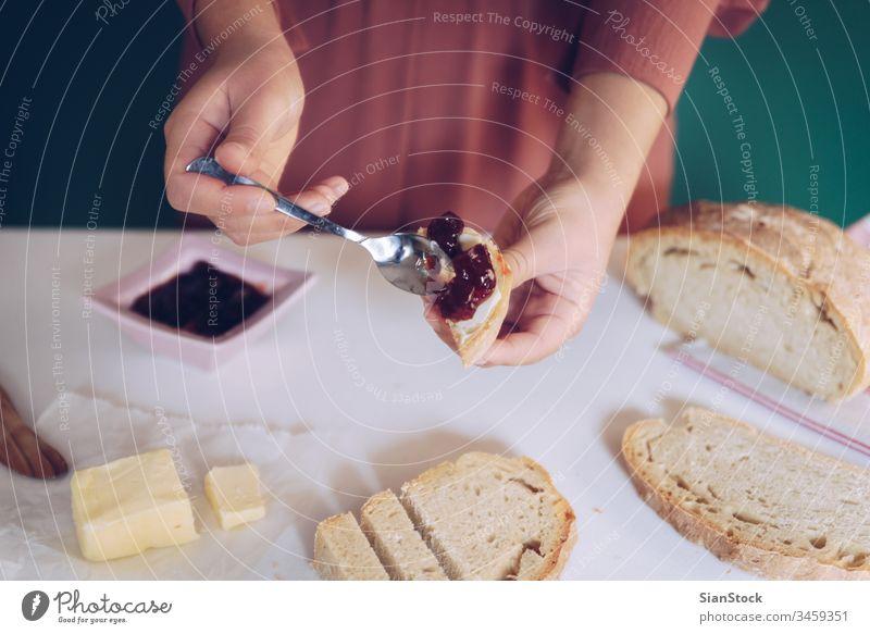 Frauen streichen von Hand Marmelade auf selbstgebackenes Brot Herstellung Küche grün Hintergrund Kleid Murmel heimwärts geröstet Löffel Tisch Kalorien Essen