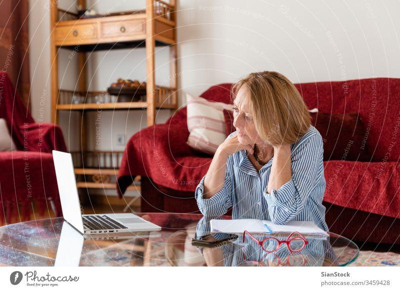 Senioren mittleren Alters, die zu Hause am Computer arbeiten Frau Laptop reif Menschen eine Person Lifestyle benutzend Brille attraktiv sich[Akk] entspannen