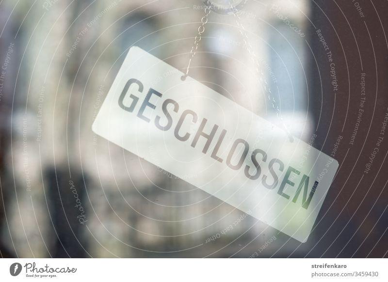 """""""Geschlossen"""" steht auf dem Schild, das innen an der Glastür hängt, während sich die Umgebung im Glas spiegelt Laden Geschäft geschlossen Gebäude Corona"""