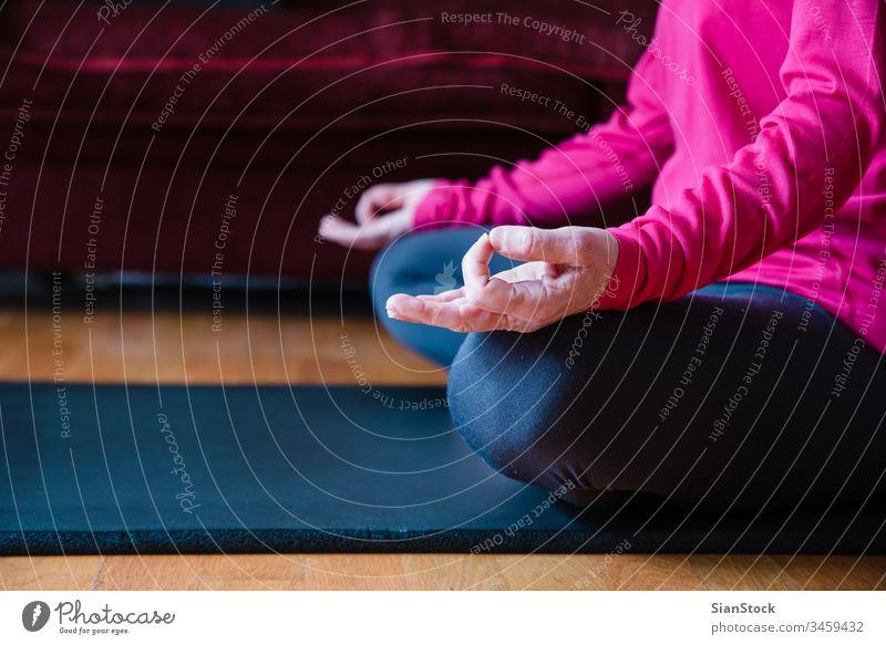 Nahaufnahme der Hände einer Frau mittleren Alters, die in Lotusstellung auf einer Yogamatte in ihrem Wohnzimmer sitzt. Biegen Schönheit Training Europäer
