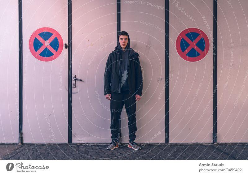 junger Mann steht zwischen zwei Parkverbotsschildern Jugendlicher Erwachsener attraktiv schön Schönheit Junge lässig Kaukasier Nahaufnahme Selbstvertrauen