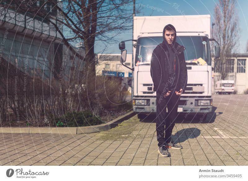 junger Mann mit Rucksack steht vor einem Lastwagen Teenager Lifestyle Lastkraftwagen Porträt aeria Architektur schön schwarz Junge Gebäude lässig Kaukasier