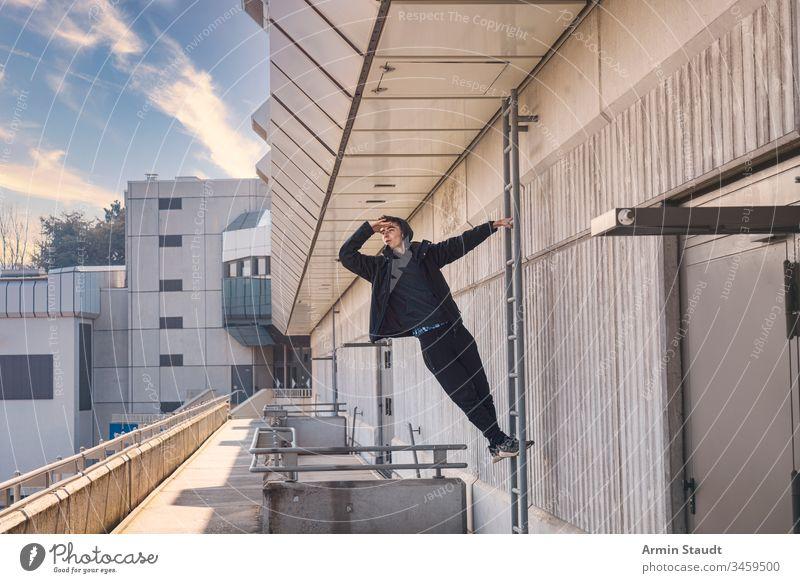 junger Mann, der auf einer Leiter herausschaut schön Junge Gebäude lässig Kaukasier Klettern Beton selbstbewusst Auge Hand Laufmasche Lifestyle Blick