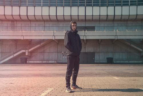 Porträt eines jungen Mannes mit schwarzem Kapuzenpulli Architektur schön Junge Gebäude lässig selbstbewusst Lifestyle Blick männlich Model im Freien Ort
