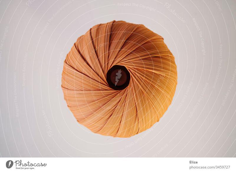Eine runde Lampe aus Stoff mit Falten von unten, grafisch, orange, cremefarben, Kreis Sonne Anus Po gelb Licht Menschenleer abstrakt Farbfoto Farbe