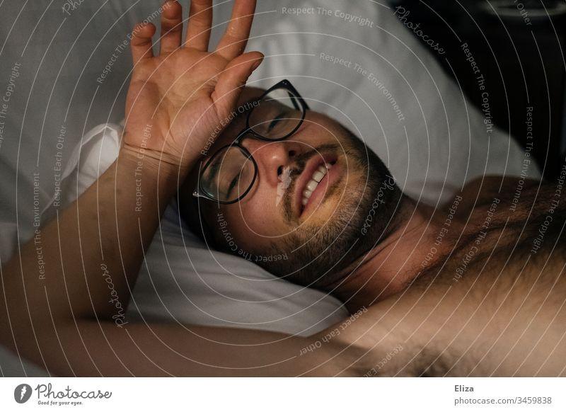 EIn Mann mit Bart und Brille, der gemütlich und verschlafen im Bett liegt und sich mit der Hand an die Stirn fässt fiebrig Fieber lächeln krank Porträt