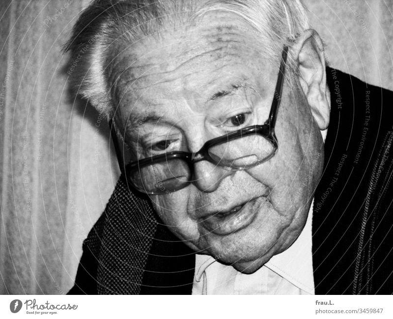 Lebhaft blickte der alte Mann über den Rand seiner bifokalen Brille in einen freudigen  Tag. Senior Männlicher Senior 1 Innenaufnahme Freude Schwarzweißfoto