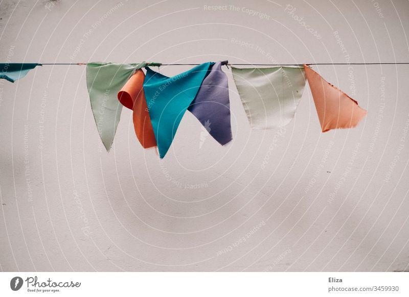 Eine bunte Wimpelkette in pastellfarben vor einer Hauswand Dekoration & Verzierung pastellton zerfleddert kaputt Party hübsch Geburtstag Feste & Feiern