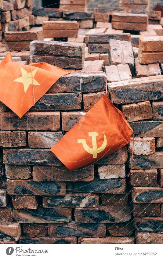 Die vietnamesische Flagge neben einer Fahne mit Hammer und Sichel, was den kommunistischen Staat symbolisiert, vor einem Haufen mit roten Ziegelsteinen