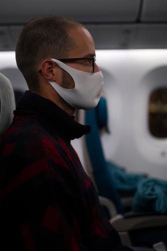 Mann sitzt während der Corona Pandemie mit Gesichtsmaske im Flugzeug Maske Stoffmaske Coronavirus Prävention Virus Mundschutz COVID Infektionsgefahr Gesundheit