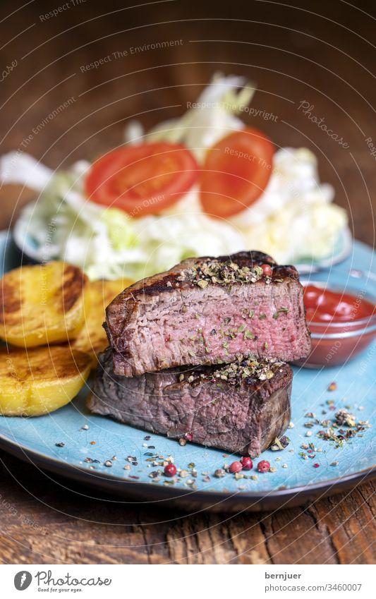 gegrilltes Steak auf dem Teller Rinderfilet Scheibe halb Hälfte habliert Kartoffel Salat Tomate mittel ketchup fettlos grillen Abendessen Mahlzeit Salz Kraut