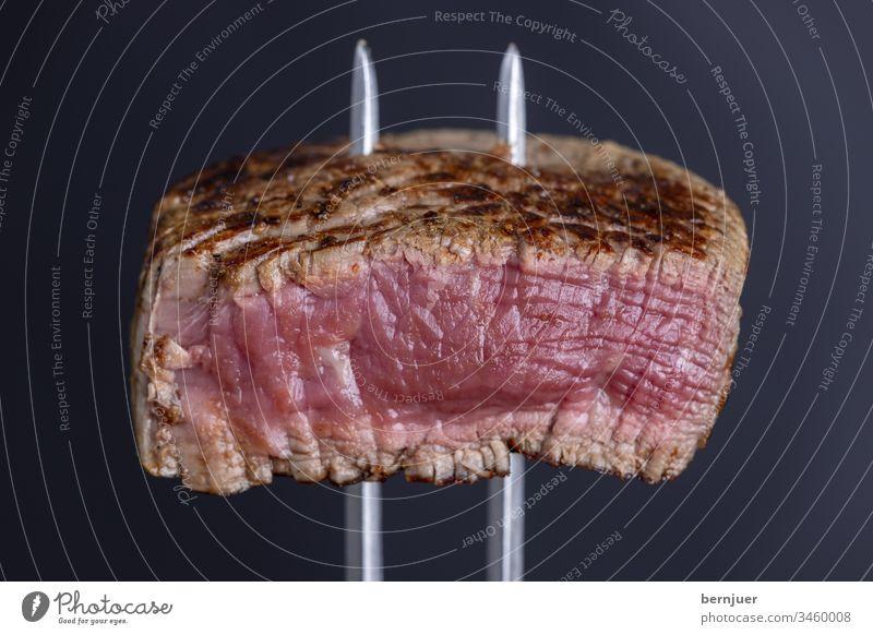 gegrilltes Steak auf einer Fleischgabel close-up besteck sirloin steak braten Hintergrund weiß geschnitten rot essen geröstet saftig Qualität Abendessen Essen