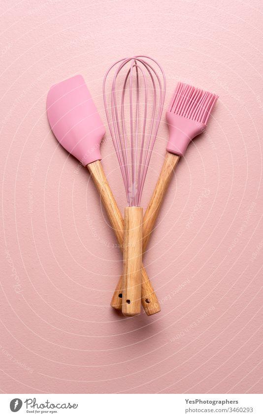 Backwerkzeuge auf einem rosa Tisch. Küchengeräte flachliegend obere Ansicht backen Backutensilien Bürste Sauberkeit farbenfroh Essen zubereiten Gerät