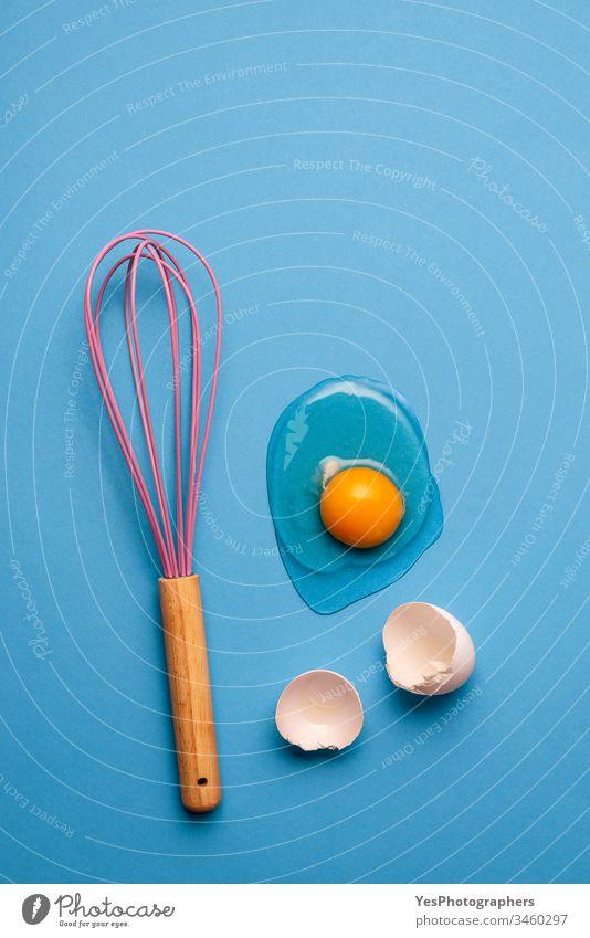 Knick-Ei und Schneebesen als Backkonzept. backen blau Sauberkeit farbenfroh Konzept Essen zubereiten Knickerei Eigelb Eierschalen flache Verlegung Lebensmittel