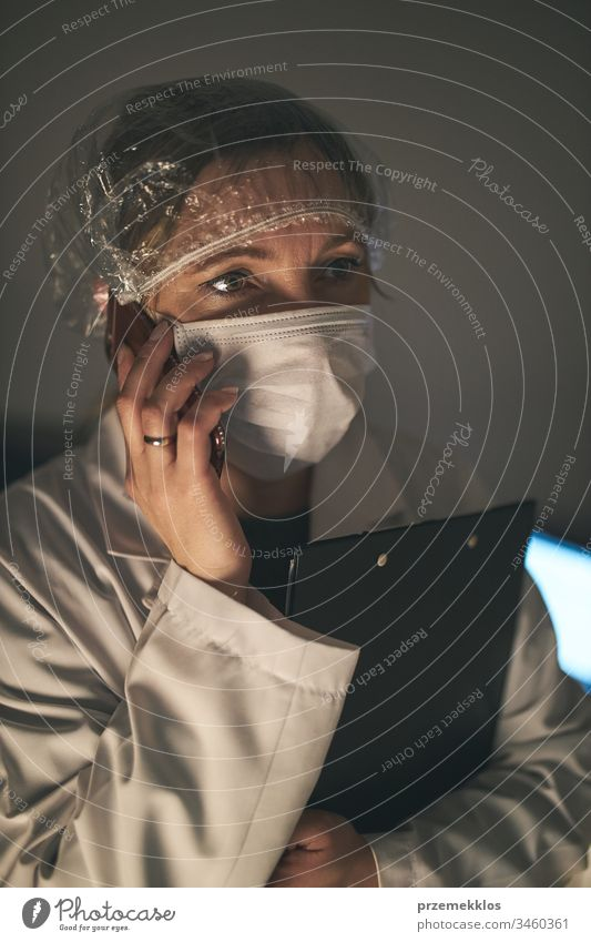 Telefonierender Arzt. Krankenhauspersonal arbeitet im Nachtdienst. Frau trägt Uniform, Mütze und Gesichtsmaske, um eine Virusinfektion zu verhindern. Infektion