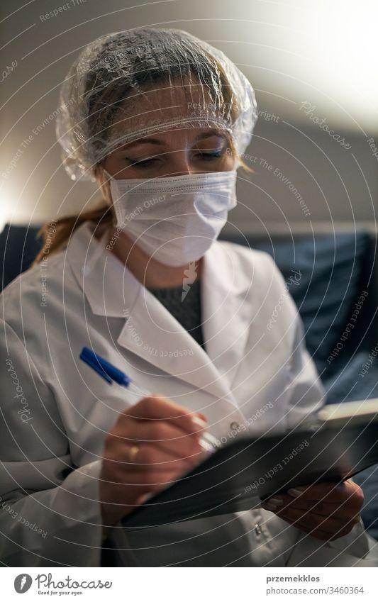 Arzt, der ein Dokument ausfüllt. Krankenhauspersonal arbeitet im Nachtdienst. Frau trägt Uniform, Mütze und Gesichtsmaske, um eine Virusinfektion zu verhindern.