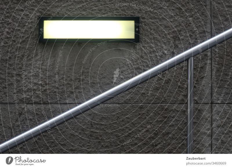 Moderner Handlauf führt nach oben, vor strukturierter Betonplatte und rechteckiger Leuchte Geländer Treppe Wand Mauer Platten Metall modern urban Menschenleer