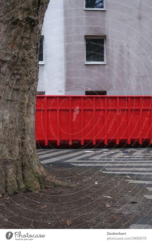 Roter Container steht vor trister Hausfassade mit leerem Fenster, davor ein Baum rot Baumstamm Ausgangssperre Fassade grau Menschenleer Tag Gebäude Bauwerk