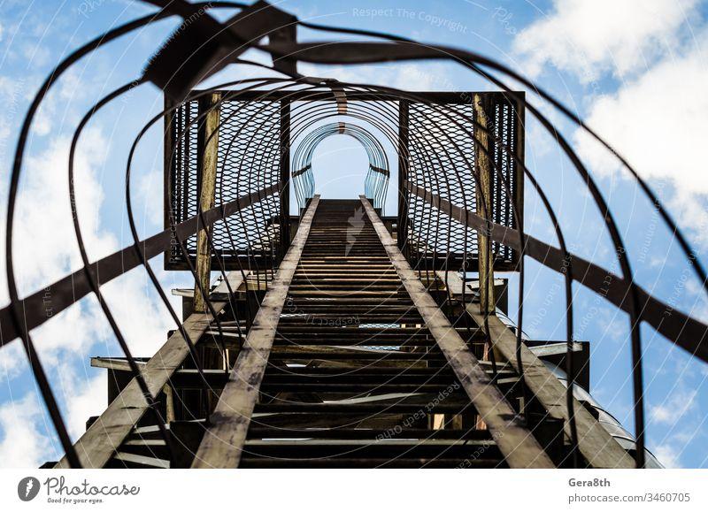alte rostige Treppe mit Schäden gegen den blauen Himmel und die Wolken Blauer Himmel Aufstieg grau Grunge industriell bügeln Eisentreppe Laufmasche Linie Linien