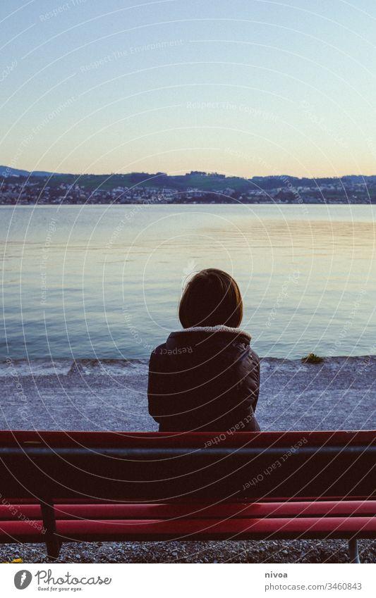 Junge auf Bank am See Sitzbank Dämmerung Abendstimmung ruhig friedlich Frühling Zürich See isolation allein Einsam Außenaufnahme Himmel Einsamkeit einsam