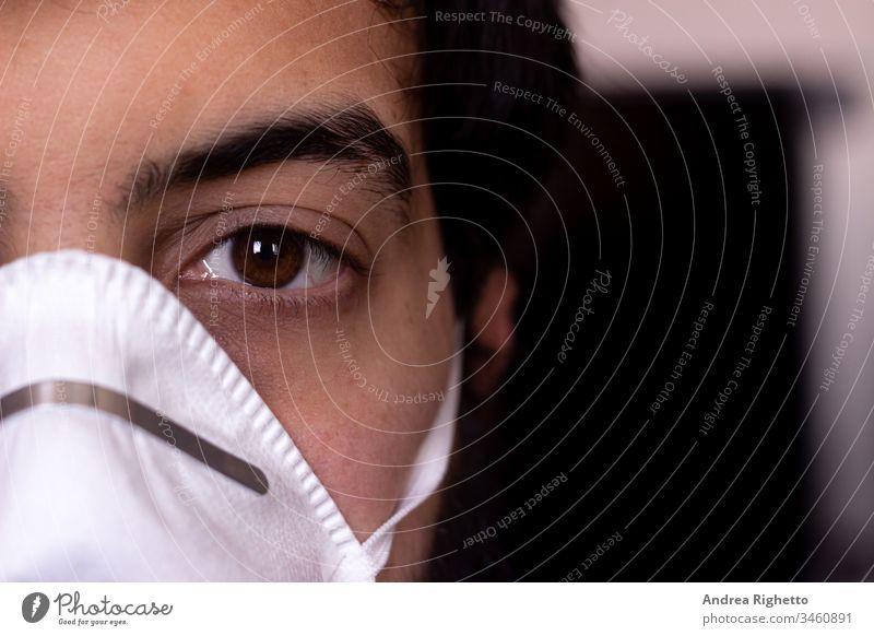 Halbporträt eines jungen kaukasischen Erwachsenen mit einer weißen Maske. Kopierfeld rechts. Mann schaut in die Kamera Erwachsener Air Junge Pflege Kaukasier