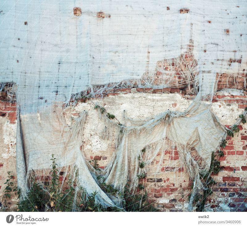 Nach dem Sturm Wand Mauer Steine Backstein Fassade alt heruntergekommen Plane Schutz Bauplane zerschlissen Löcher schadhaft zerzaust zerfleddert fadenscheinig