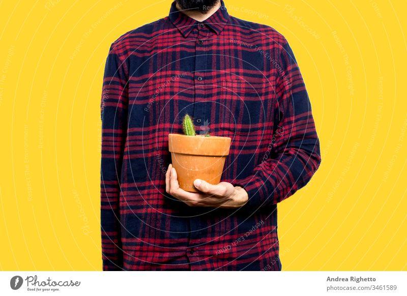 Junger Mann hält mit der linken Hand eine kleine Kaktuspflanze. Er befindet sich in der Mitte des Bildes. Der Hintergrund ist gelb. Der Kaktus befindet sich in einer braunen Vase