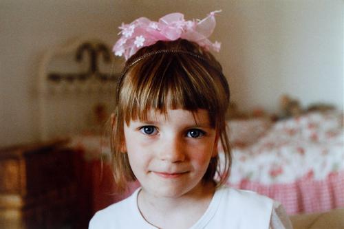 Kleines Mädchen freut sich glückselig über ihren Haarschmuck aus rosa Blumen und ist verkleidet als Prinzessin mit Krone aus Blüten. mädchenhaft Mädchenportrait