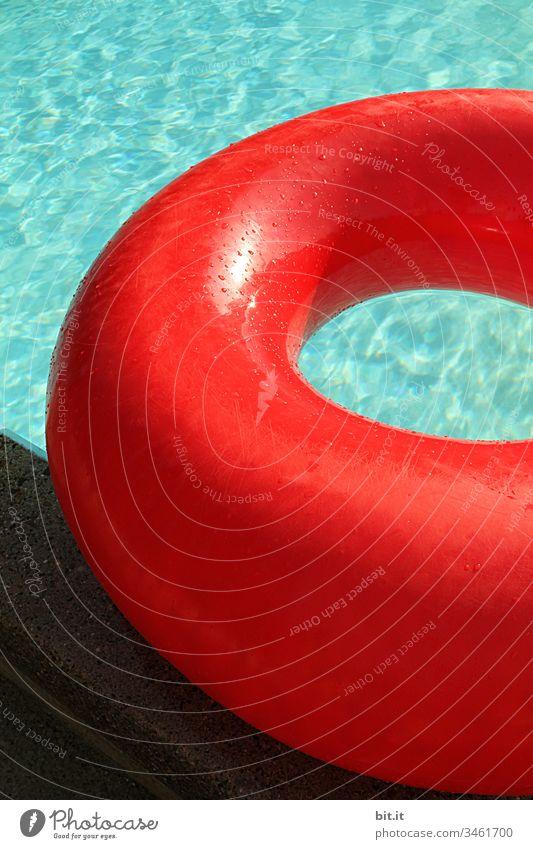 Prall gefüllt, liegt der große, rote Schwimmring am Rand vom Schwimmbecken, im türkisen Wasser. Schwimmen & Baden Schwimmbad Sommer blau Freude