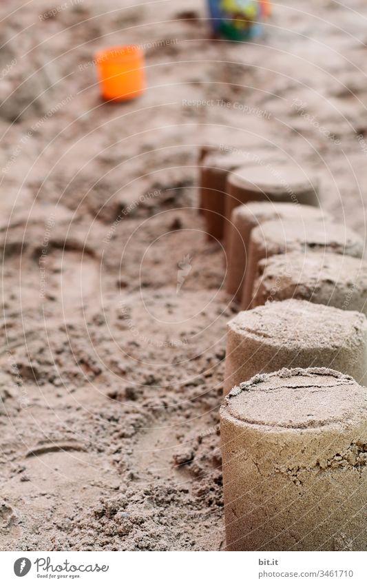 Sandkuchen oder Sandburg gebaut mit Sand am Strand oder im Sandkasten, im Urlaub, mit Eimer und Sandförmchen im Hintergrund. Küste Spielen Bauwerk