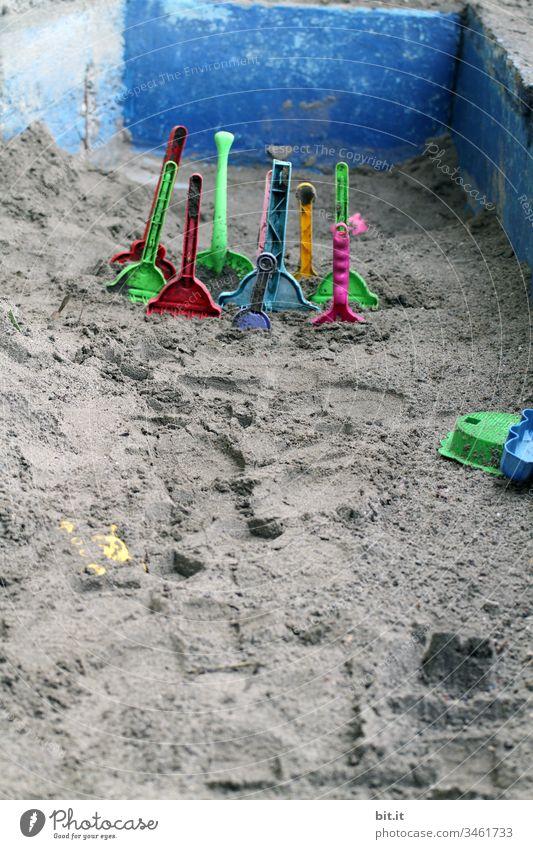 Viele, bunte Sandschaufeln aus Plastik stecken im Sand, in einem leeren Sandkasten aus Stein, im Urlaub. Sandelschaufel Schaufel Spielen Spielzeug Kindheit