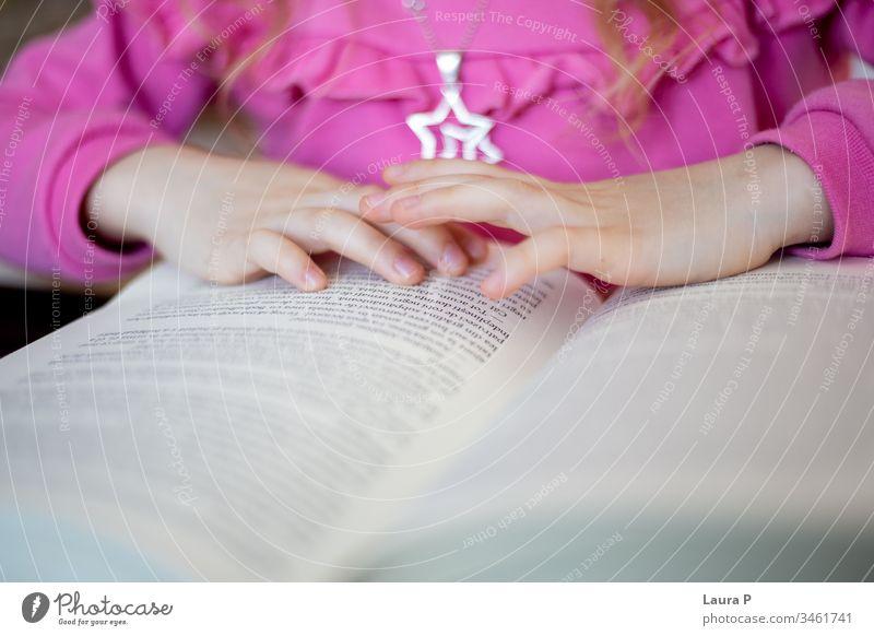 Nahaufnahme der Hände eines kleinen Mädchens beim Lesen bezaubernd achtsam aufmerksam schön blond Buch gelangweilt Kaukasier Kind Kindheit clever konzentriert
