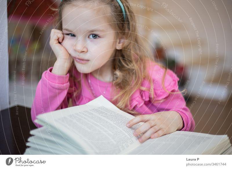Kleines blondes Mädchen müde und gelangweilt vom Lesen und Hausaufgaben machen bezaubernd achtsam aufmerksam schön Buch Kaukasier Kind Kindheit clever