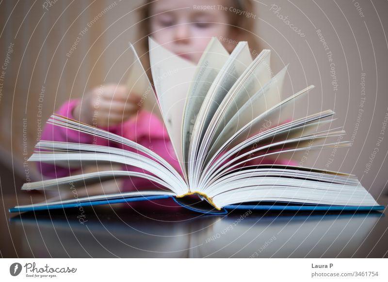 Kleines blondes Mädchen liest und macht Hausaufgaben bezaubernd achtsam aufmerksam schön Buch gelangweilt Kaukasier Kind Kindheit clever Nahaufnahme