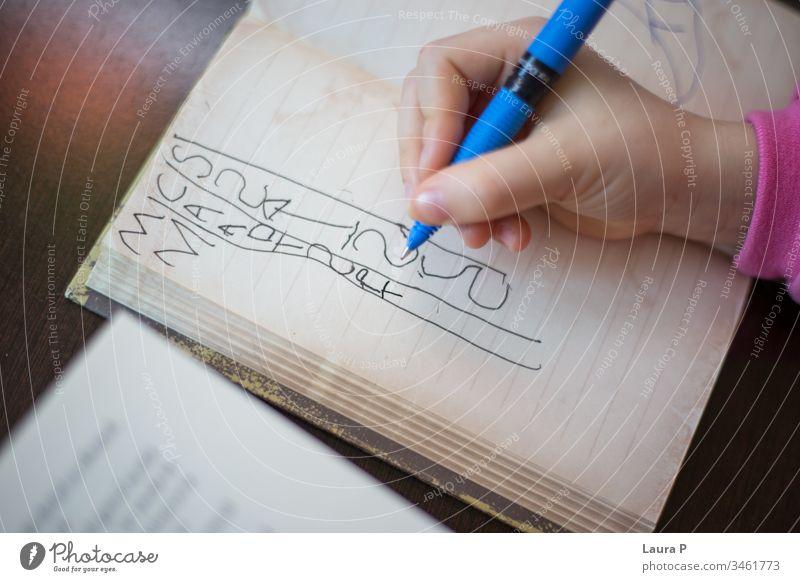 Nahaufnahme der Handschrift eines Kindes in einem Notizbuch bezaubernd achtsam aufmerksam schön blond Buch gelangweilt Kaukasier Kindheit clever konzentriert