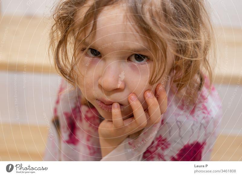 Nahaufnahme einer verärgerten kleinen Blondine, die ihr Kinn in der Hand hält bezaubernd allein wütend Schlechte Laune schön gelangweilt blond Kind Kindheit