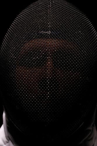 Fechtender Mann Athlet Sportler sportlich Hintergrund schwarz schließen Bekleidung Konkurrenz dramatisch Zaun kämpfen Kopf Beleuchtung Blick männlich Mundschutz