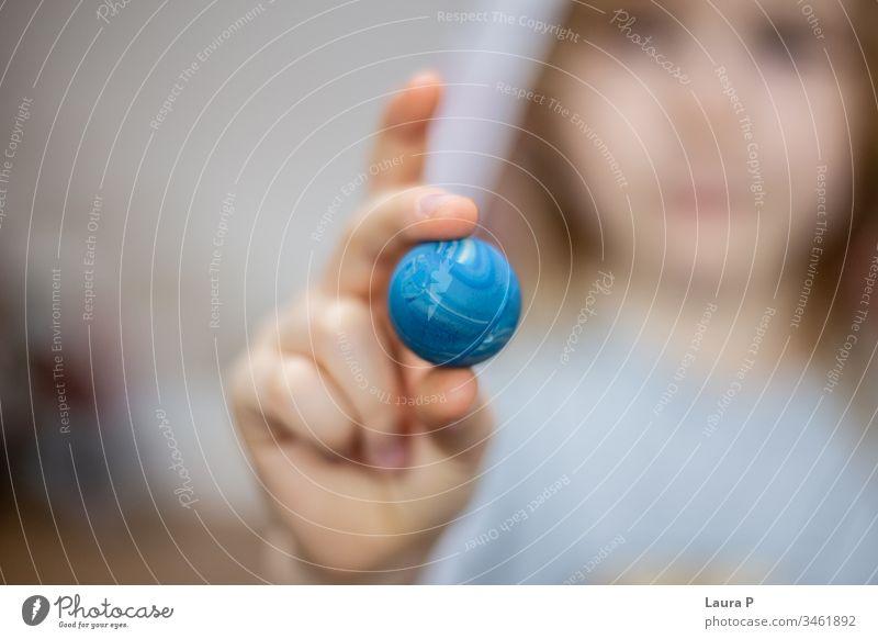 Nahaufnahme von Kinderfingern, die einen kleinen blauen Ball halten verschwommener Hintergrund Unschärfe abschließen Familienzeit spielen zeigend Pressen Freude
