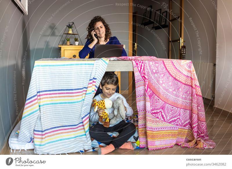 Mutter arbeitet zu Hause, während ihr Sohn spielt Erwachsener Baby Junge Business Kind Kinderbetreuung Kindheit Wohlbefinden von Kindern Computer Coronavirus
