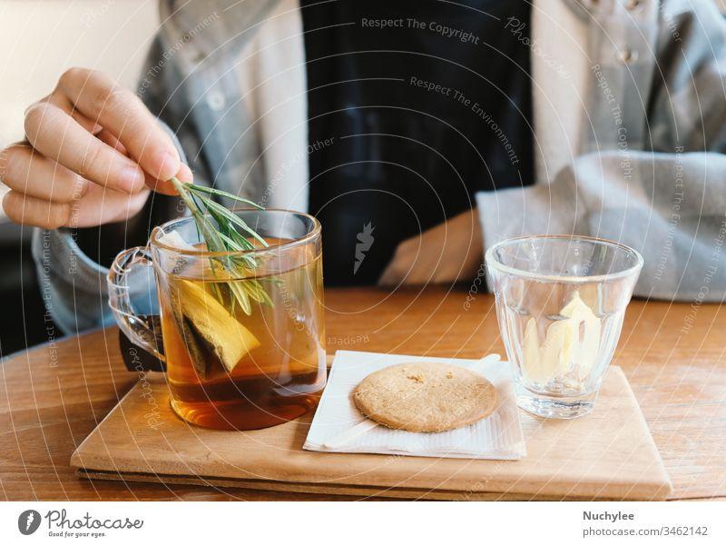 Nahaufnahme der Hand eines jungen Mannes, der Rosmarin in den heißen Tee für die Teepause am Nachmittag tut, entspannend und gemütlich zu Hause Nachmittagstee
