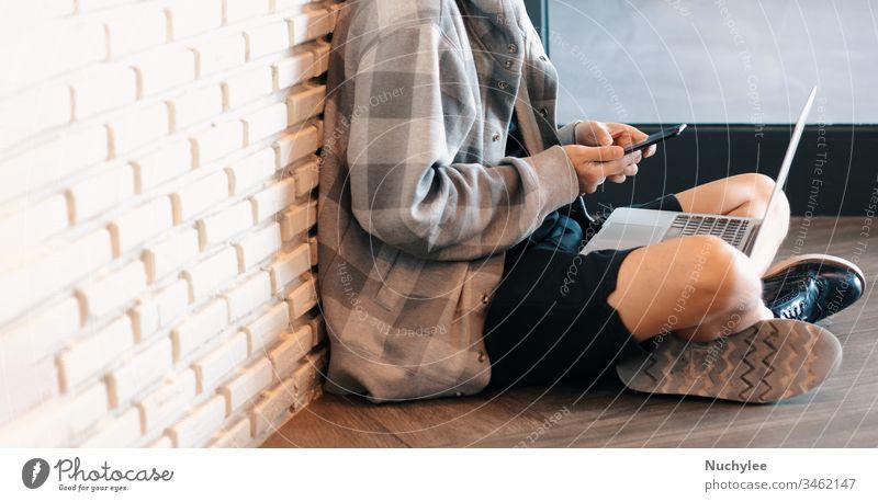 Junger tausendjähriger Mann sitzt auf dem Boden und lernt zu Hause während der Selbstquarantäne vor der Covid-19- und Coronavirus-Pandemie Online-Unterricht über Smartphone und Laptop