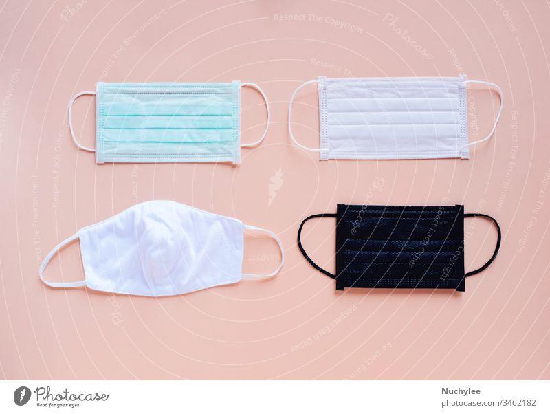 Flächiges Auflegen von Hygienemasken verschiedener Art und Farbe auf hellem, pfirsich-orangem Farbhintergrund, Gesundheitsvorsorge und Verhinderung der Ausbreitung des pandemischen Covid-19 und Coronavirus,