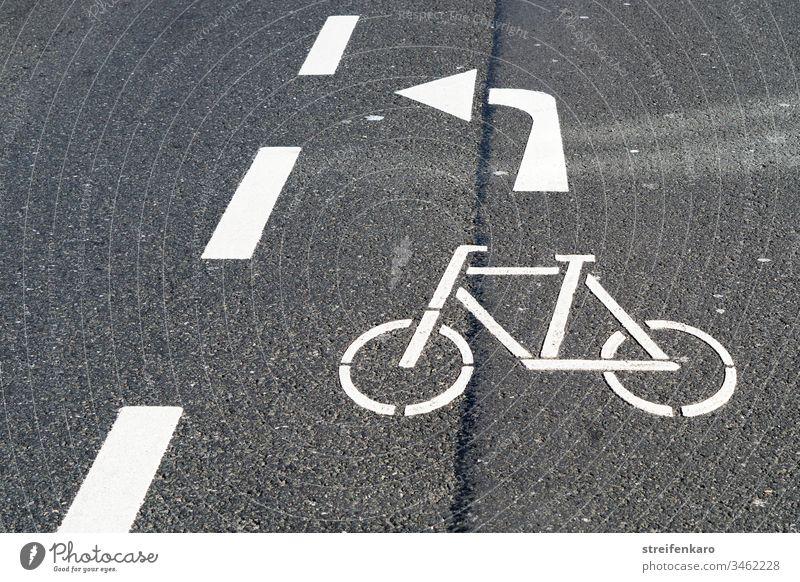 Radfahrer bitte nach links durch die Lücke abbiegen, bedeutete der weiße Pfeil der Fahrbahnmarkierung Straße Straßenmarkierung grau Asphalt Radfahren Radweg