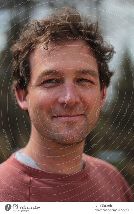 Porträt von einem Mann Locken kurze haare kurzhaarig blaue augen Dreitagebart Pullover grinsen strubelig Gesicht