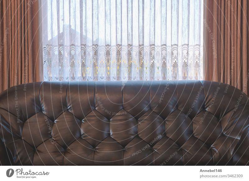 Altes braunes Ledersofa in der Nähe des Fensters im Vintage-Wohnzimmer, antikes Retro-Design. renovierungsbedürftig Innenbereich altehrwürdig Antiquität Sofa