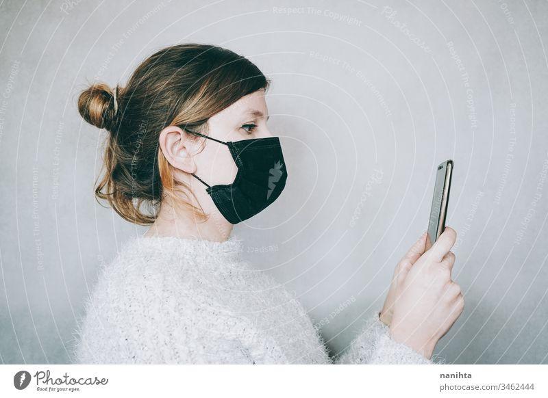 Junge Frau, die eine Maske trägt, während sie ihr Smartphone benutzt Bund 19 COVID Coronavirus Virus Atem Pandemie Mundschutz Krankheit infiziert Mobile Telefon